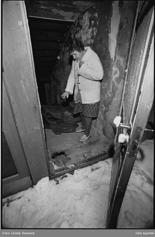 Eldre dame innenfor døra til kjelleren. Fotografiet er fra prosjektet og boka ''Oslo-bilder. En fotografisk dokumentasjon av bo og leveforhold i 1981 - 82''. Kontakt Samfoto/Scanpix ved ev. bestilling av kopier.