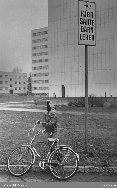 """Gutt med sykkel foran høyblokk. Skilt: """"Kjør sakte barn leker."""" Fotografiet er fra prosjektet og boka ''Oslo-bilder. En fotografisk dokumentasjon av bo og leveforhold i 1981 - 82''. Kontakt Samfoto ved ev. bestilling av kopier."""