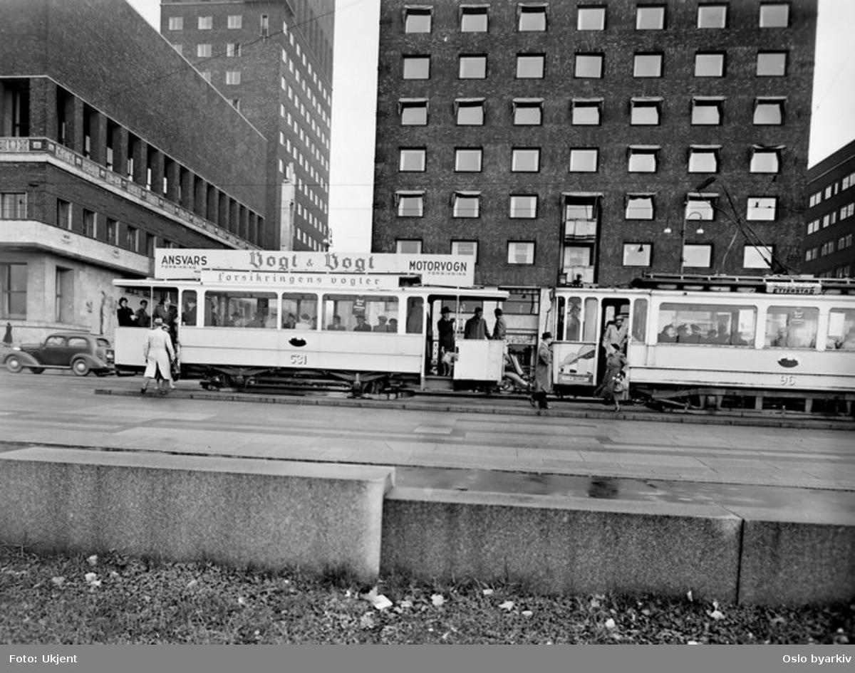Oslo Sporveier. Trikk tilhenger (fra 1899) type kommunal ombygd (1919) til vogn 531 og motorvogn 96 type SS lang (fra 1914) linje 16, Vålerenga-Skøyen, ved stoppestedet Tordenskiolds plass. Takreklame for assuranseforretningen Vogt & Vogt. Rådhusets østre del. Forretningsbygg. Bilde tatt en gang mellom 1950-1955.