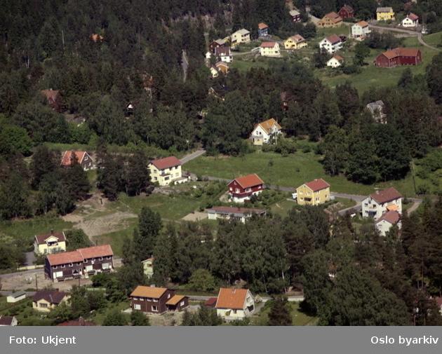 Nordstrandveien halvt skjult ved skog bak i bildet. (Flyfoto)