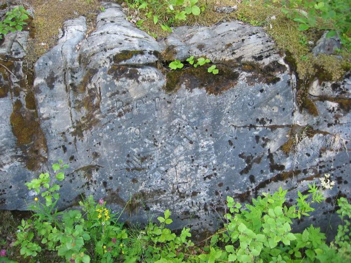 Inskripsjon i berget. Flere bokstaver er uleselige. Figur av hakekors inne i noe som ligner et omvendt skjold er synlig.