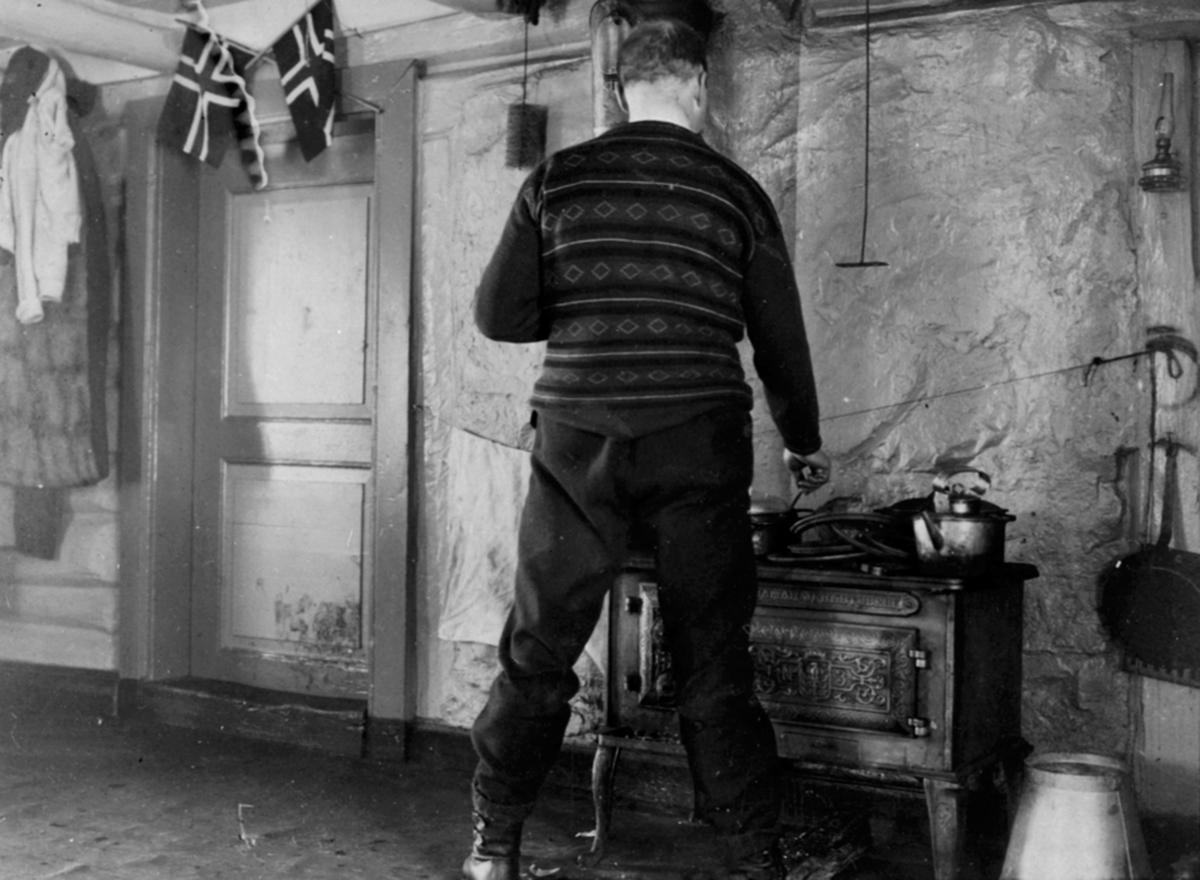Interiør, kjøkken med vedkomfyr no. 3 fra Hamar Jernstøperi. Mann med stekepanne lager mat på ovnen. Sinkbøtte, norske flagg.