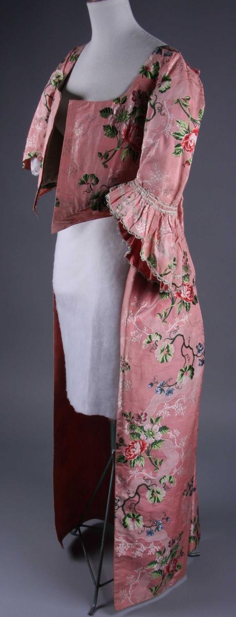 Gallakjole av laksrosa, tykkripssilke med brochert, polykromt blomstermønster. Den består av overkjole med Watteau-folder i ryggen, ettersittende liv og 3/4-lange ermer med kappe nedert, og et underskjørt av samme stoff, delvis klippet i stykker.  Watteau-foldene på overkjolen springer ut fra et smalt, lissebesatt bærestykke og faller løse helt ned til gulvet. Underste fold er sydd fast til livet fra midjen og opp og foldene er nestet sammen like oppe ved bærestykket. Skjørtet er lagt i tette folder på hver side inntil sidesømmene og sydd fast til livet. Det består av fire bredder og er rett avskåret nedentil. Forstykkene er fri, litt sidere enn ryggen og løper ned i en spiss foran. Utringingen er firkantet på ryggen, vid og dyp foran og livet lukkes ved en snøring i fôret. Det har gått lissebesatte folder eller bånd (nå avklippet) på hver side over skuldrene og nedover forstykkene. De har kanskje stått i forbindelse med en hempe som ennå finnes nederst, et stykke fra sidesømmene. Livet er avstivet med spiler foran og i ryggen. Spilene er sydd inn mellom to lag fôr, et av rosa, vokset lerret, og det innerste av naturfarget linlerret. Det er fôr av rosa, vokset lerret også i skjørtet og ermene. Disse er litt rynket på skuldrene, skrått avskåret nederst, og ved albuen er det sydd på en tett rynket kappe betydelig sidere ytterst enn innerst, 7,8-21 cm. Kappen er pyntet med ialt fire rader silkelisser og er fôret med rosa taft. (Kappen mangler på det ene ermet.) Livet har preserver av ullstoff fylt med vatt.