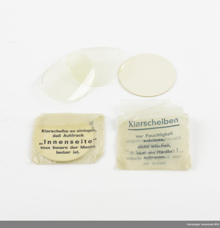 Komplett utstyrt Wehrmact model 1938 gassmaske-sett. Maske og stropper i tøystoff. Brillekomponter i plast. Nederst i beholderen, en tøyduk ca. 20x25 cm beregnet til brillepuss. På underside av topplokk, et lukket rom med 3 par ekstra brilleglass.