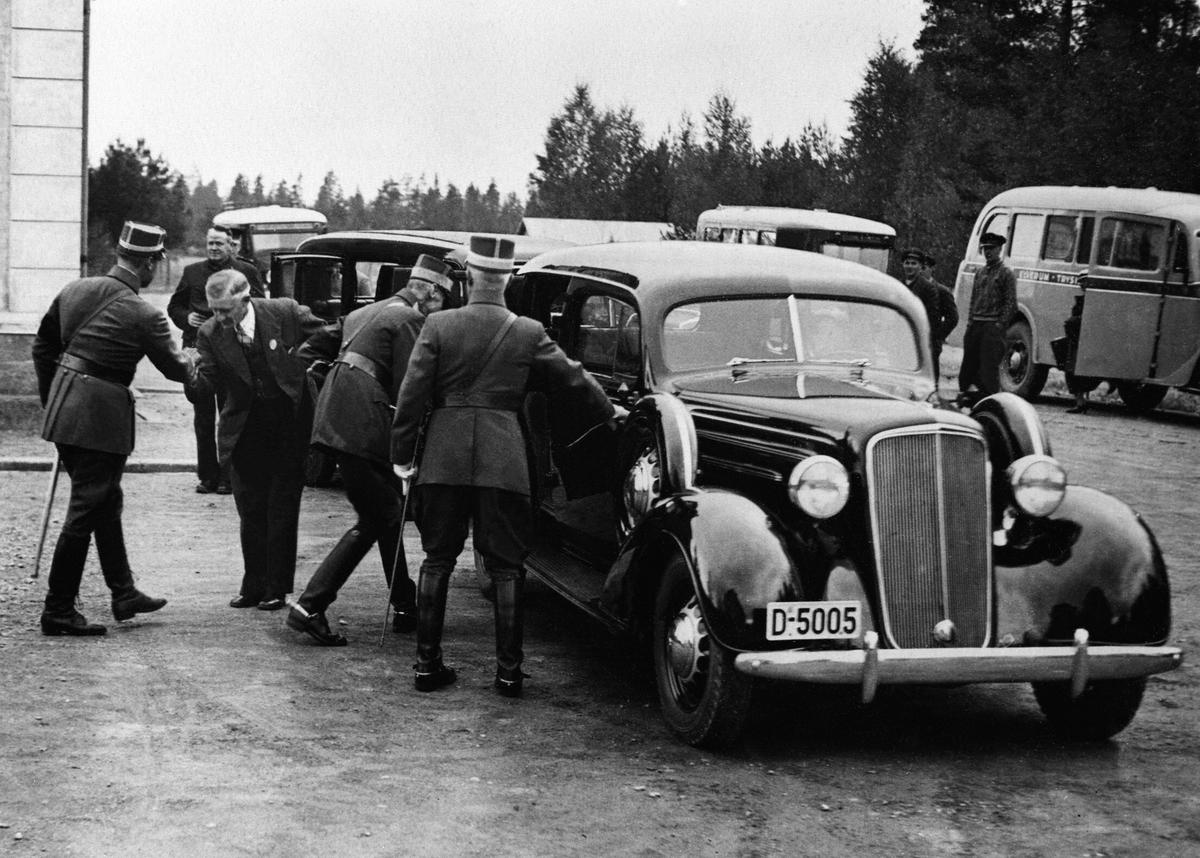 Repro. (tidligere registrert som et bilde fra 9. april, 1940, men er nok et senere besøk på Elverum, dvs etter krigen. Kronprinsen har feil lue), kong Haakon 7. , Elverum. Kong Haakon og kronprins Olav går inn i bilen til drosjeeier Vold, Chevrolet D-5005 ved skolen i Strandbygdveien. Kronprins Olav hilser på drosjeeier Vold. General Sande til høyre.  D-5005 er årsmodell 1935.