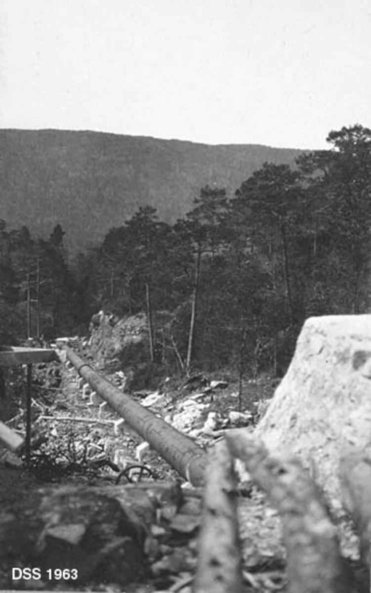 Rørledningen til det kommunale elektrisitetsverket for Os kommune i Hordaland.  Fotografiet er tatt fra demningen ved Krokvann og nedover langs rørgata, som på dette tidspunktet tydeligvis var nybygd.  En del av demningen skimtes i forgrunnen.  Rørgata består av sammenklinkete stålplater som kviler på betongfundamenter.  Traséen går gjennom et berglandskap med furuskog, der det later til å være gjort en del tilpasninger i terrenget for å skape jevnt fall.