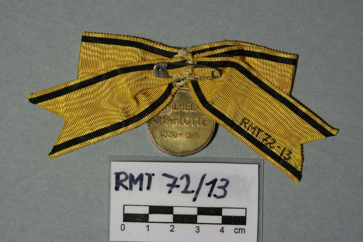 Forgylt minnemedalje. Henger i sølyfe av gul moire med sorte striper. På den ene siden kongeparets portretter i profil, haut relief. På den andre siden preget: Wilhelm/Charlotte/1886-1911.