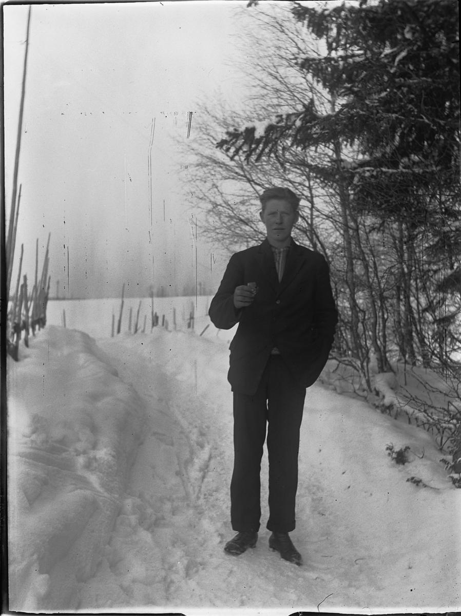 Ukjent mann ute, vinter. Holder ei pipe?