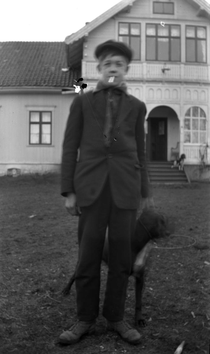 Ukjent gutt med røyk i munnen og en hund i bånd.  Ukjent hus med en hund på trappen.