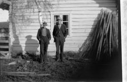 To menn utenfor et hus og en stabel med staur.