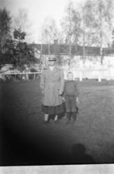 Ukjent kvinne og en gutt i en hage.
