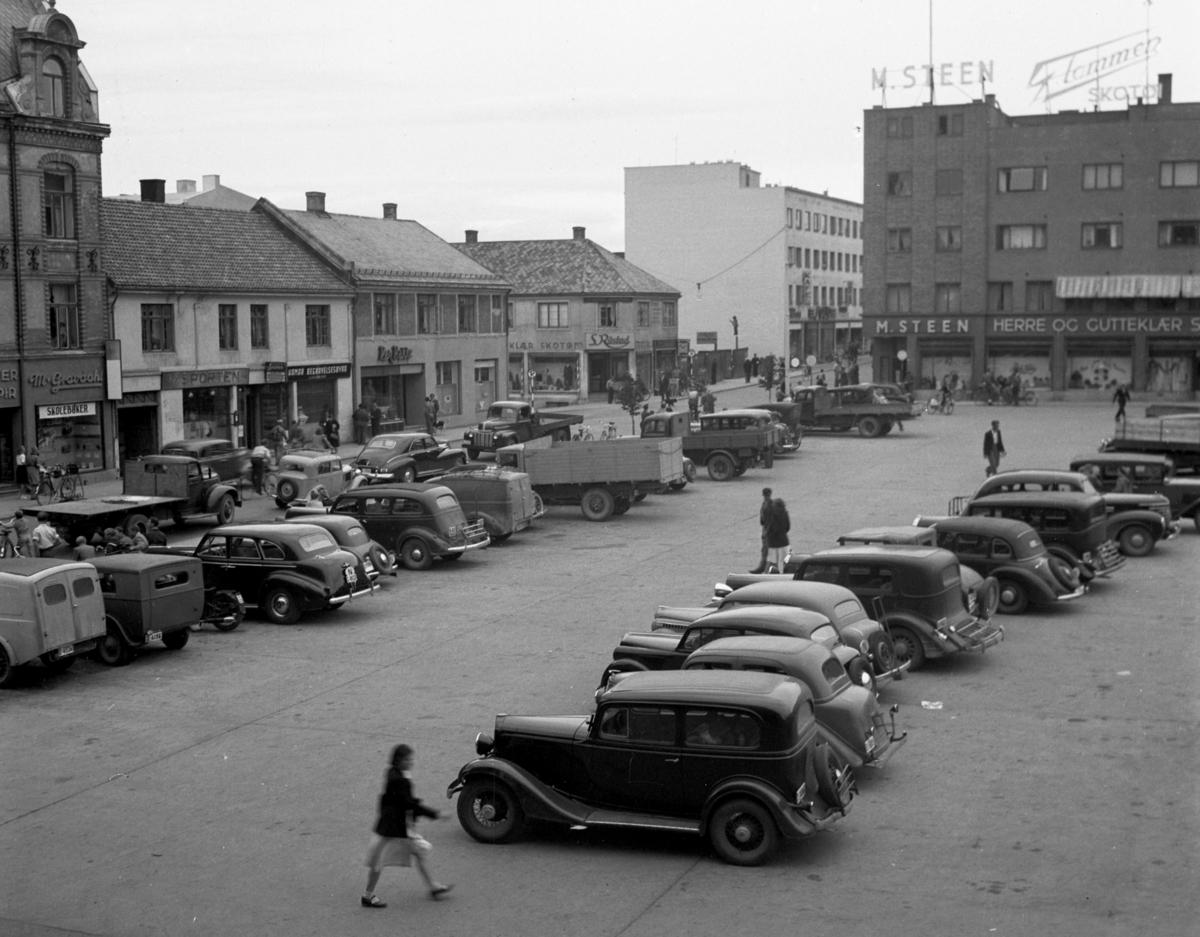 """Østre Torg, Torggata, parkeringsplass, personbiler og lastebiler parkert på torget. Foto for """"trafikk-komiteen"""" Foto Normann10. 09. 1949."""