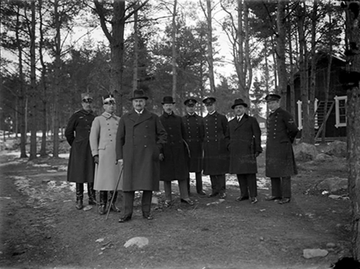 Statsminister Carl Gustaf Ekmans besök vid F 2 år 1931. Grupporträtt i skogsparti av åtta män. Officerare ur flygvapnet. Statsministern står längst fram.