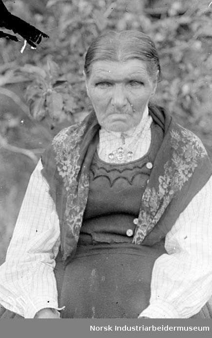 Eldre dame i bunad, sittende. Dette er muligens Sigrid Bokko.