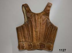 """Katalogkort:  Lifstycke af brunt kalvskinn. Snörlif med insydda styfva spröt i rygg, sidor och framtill, sex par snörhål och en snörrem af skinn i det nedersta hålet på höger sida samt tio tegellagda flikar delvis i ett stycke med lifvet, delvis tillskarfvade. Foder af grov hvit linnehväf. Tillhör den äldre kvinnodräkten, kalladt """"munkalifstycke"""". Dylika lif, men af rödt kläde och med grönkantade flikar, förekommo i bruk långt in på 1840-talet. /P.G.Vistrand/  Skinnet brunt, kraftigt. Med sammanlagt 12 insydda spröt  jämnt fördelade runt livet., snörhålen kantsydda med ljust lingarn. Foder av oblekt linne i spetskypert. Anm. Helt men väl använt, nött och fläckigt. Sådana skinnlivstycken användes framförallt till vardags, de var mycket slitstarka. /Berit Eldvik 2008-02 15Kalvskinn."""