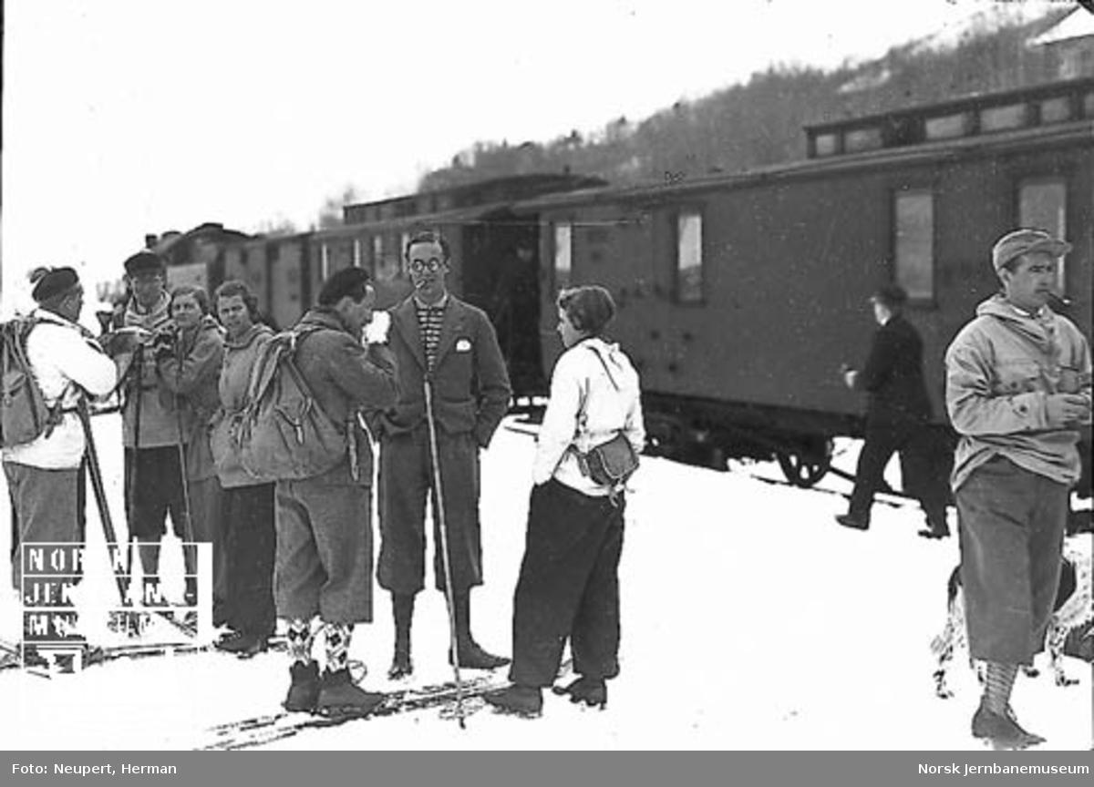 Skiturister på perrongen på Ustaoset stasjon, damplokomotiv med persontog i bakgrunnen