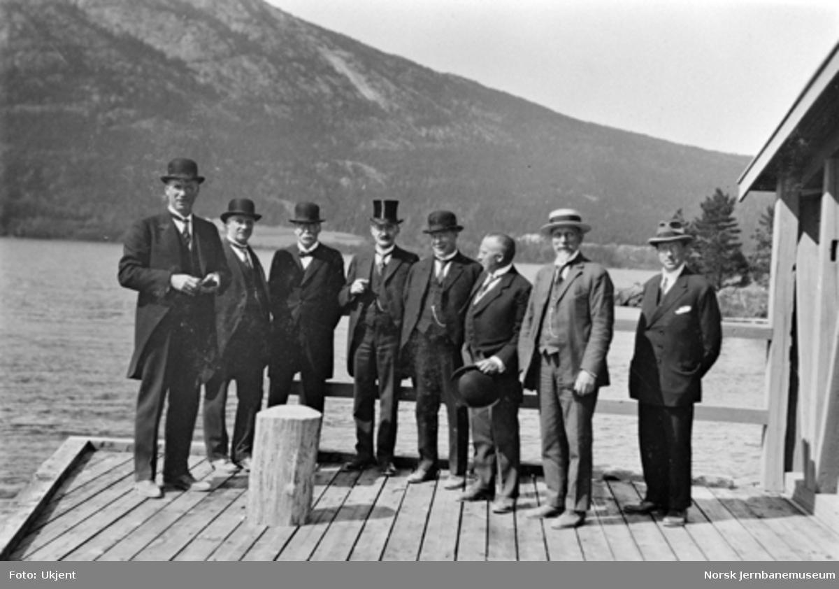 Fra åpningshøytideligheten på Sperillen stasjon : åtte menn på jernbanebrygga