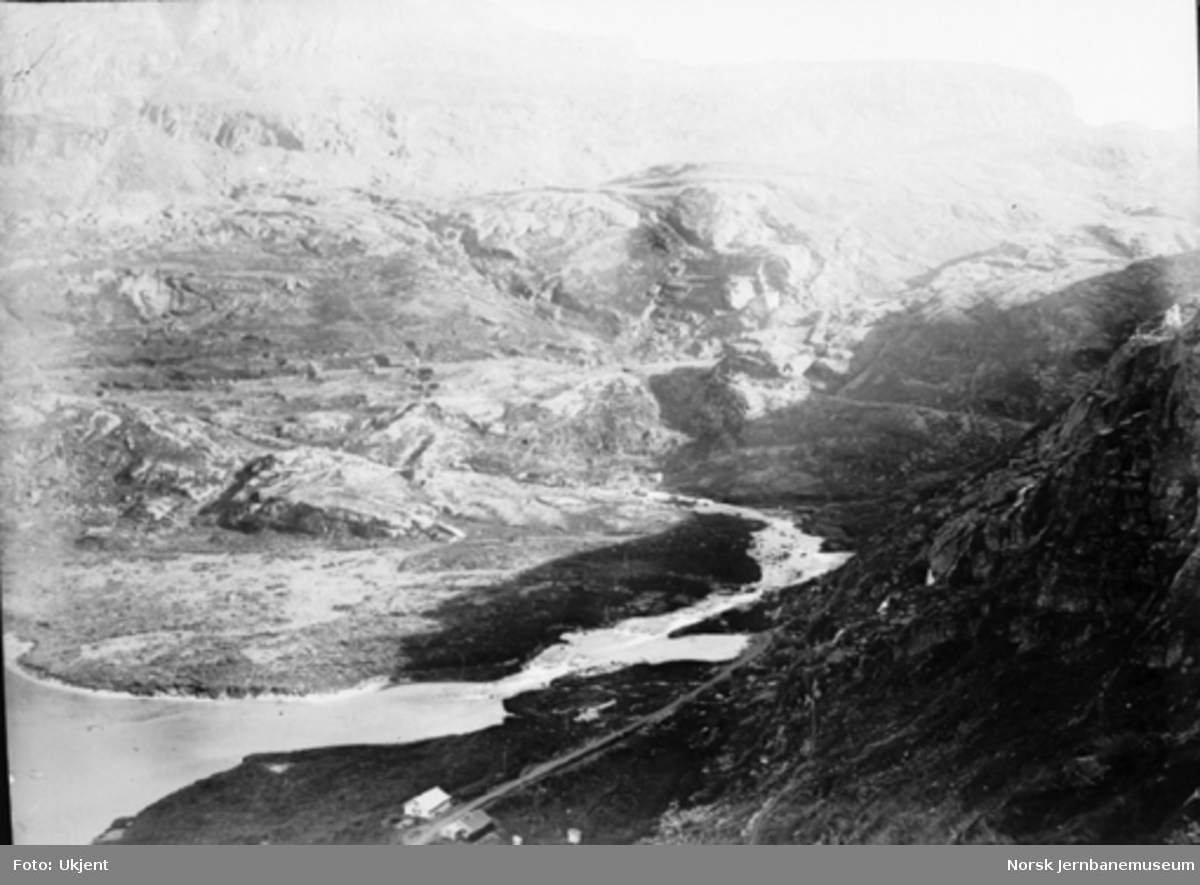 Bergensbanens anlegg; utsikt fra Seltuftbergene mot Klevejelet. Anleggsvegen svinger inn i Klevejelet, som er det trange skaret i bakgrunnen. Til høyre stillas for jernbanens løpestreng.