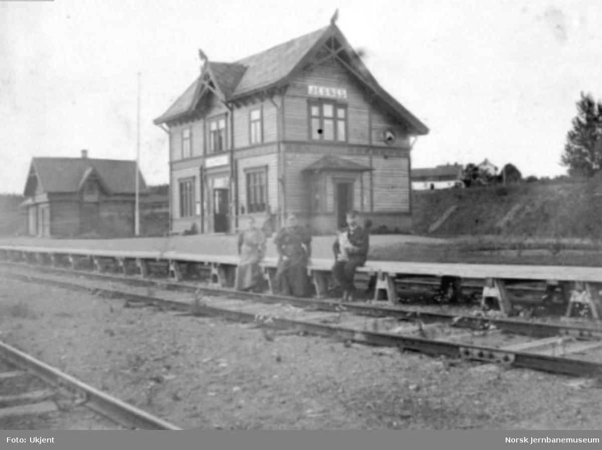 Stasjonsbygningen og godshuset på Jessnes; stasjonsekspeditøren og familien sitter på plattformkanten