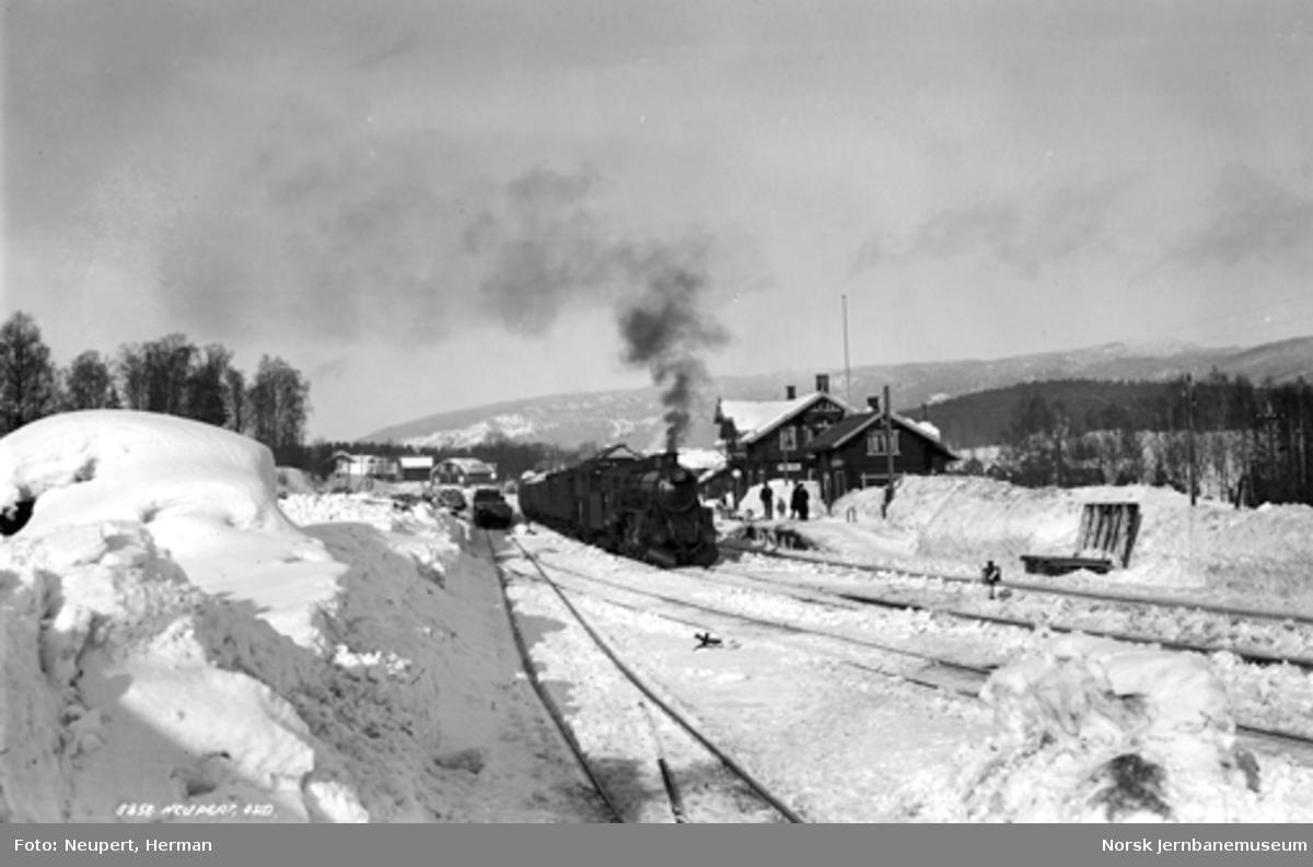 Vintermotiv fra Hakadal stasjon med damplokomotiv med persontog