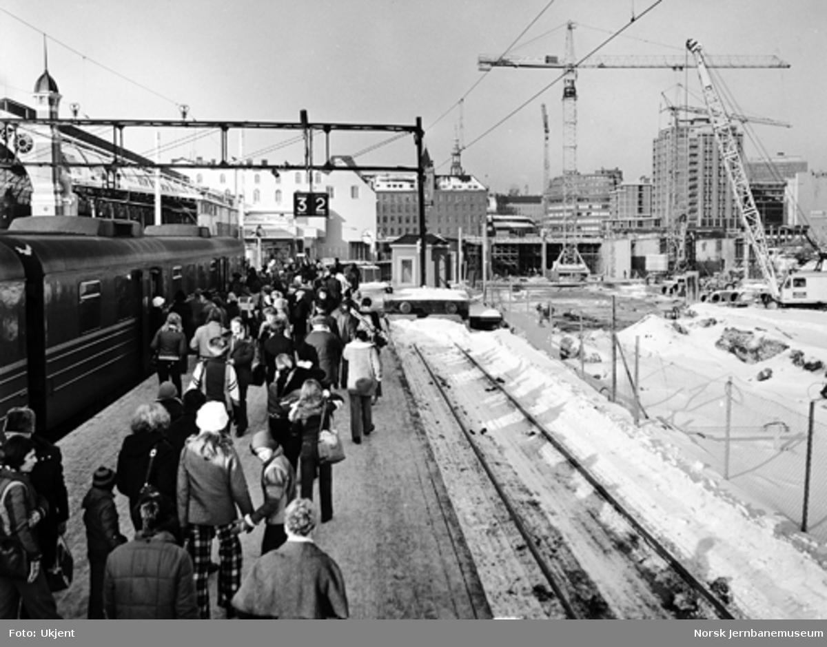 Byggingen av Oslo S : lokaltog med reisende i spor 3 og anleggsvirksomhet på Oslo S-området