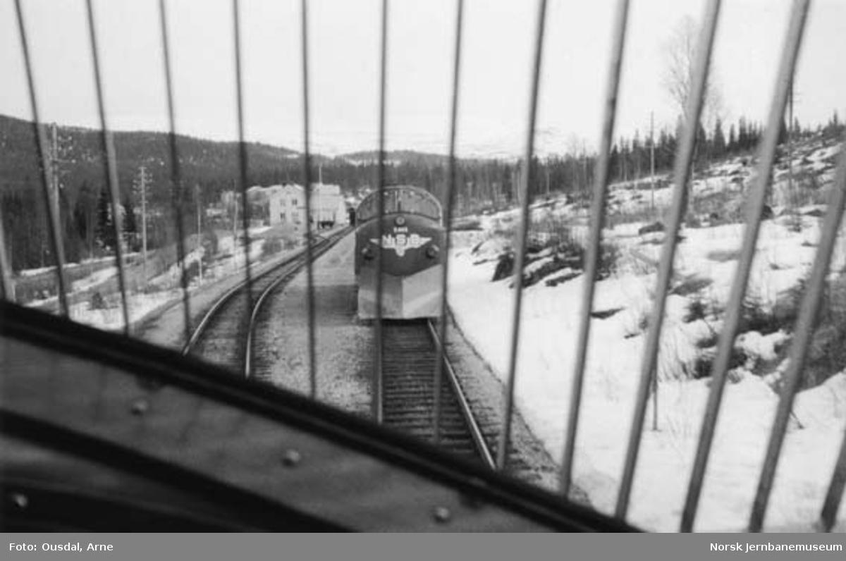 Kryssing på Namsskogan stasjon sett fra førerplassen i et diesellokomotiv. Diesellokomotiv Di 3 605 venter med motgående tog.