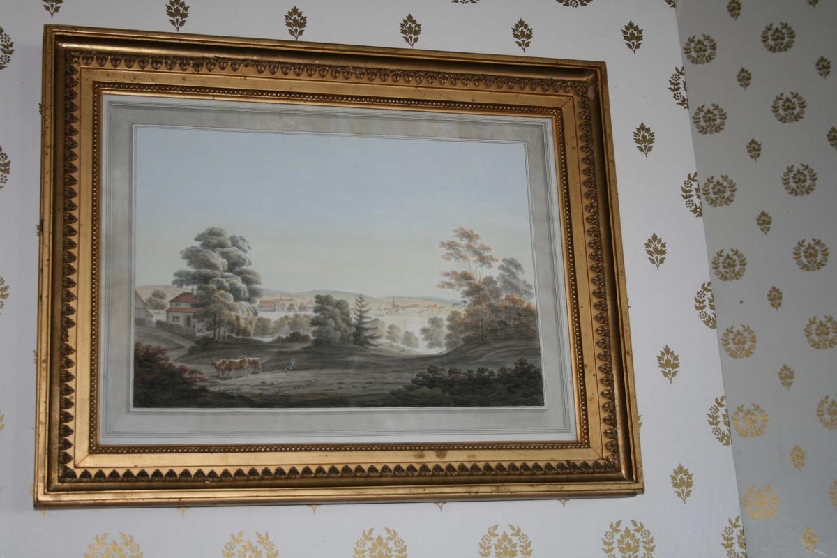 Landskap. I forgrunn er det kuer og et menneske, noen hus til venstre. Utsikt til landskap med bebyggelse i bakgrunnen.  Moss jernverk, hvor Carsten Anker vokste opp.