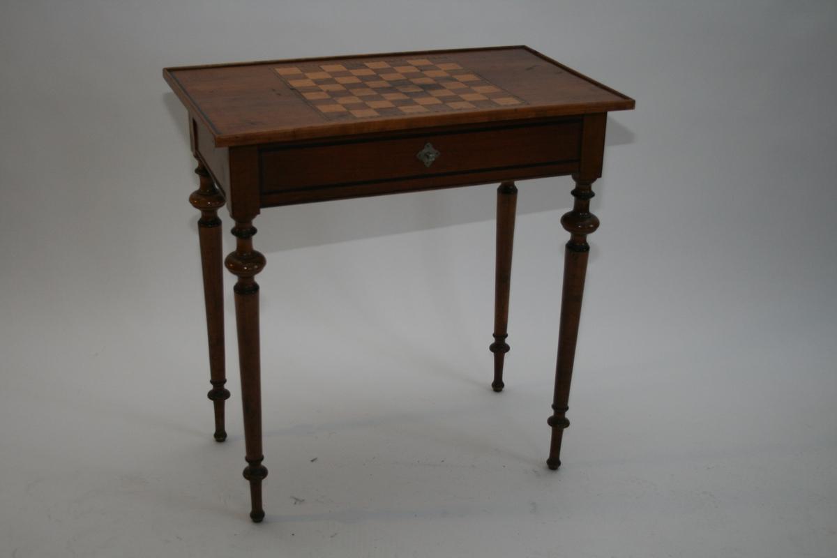 Rekangulær bordplate med innfelt sjakkbrett i lyst og mørkt tre. En skuff i sargen, dreide bein.