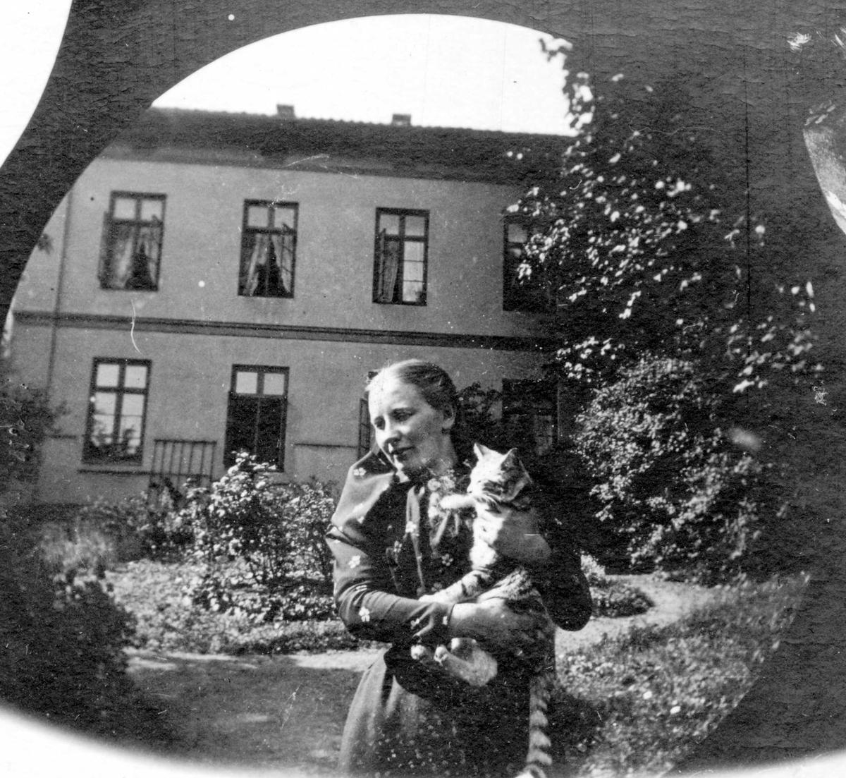 Professor Blytts stuepike og katt. Kvinne med stipet katt på armen i hage forann toetasjers hus, Oslo.