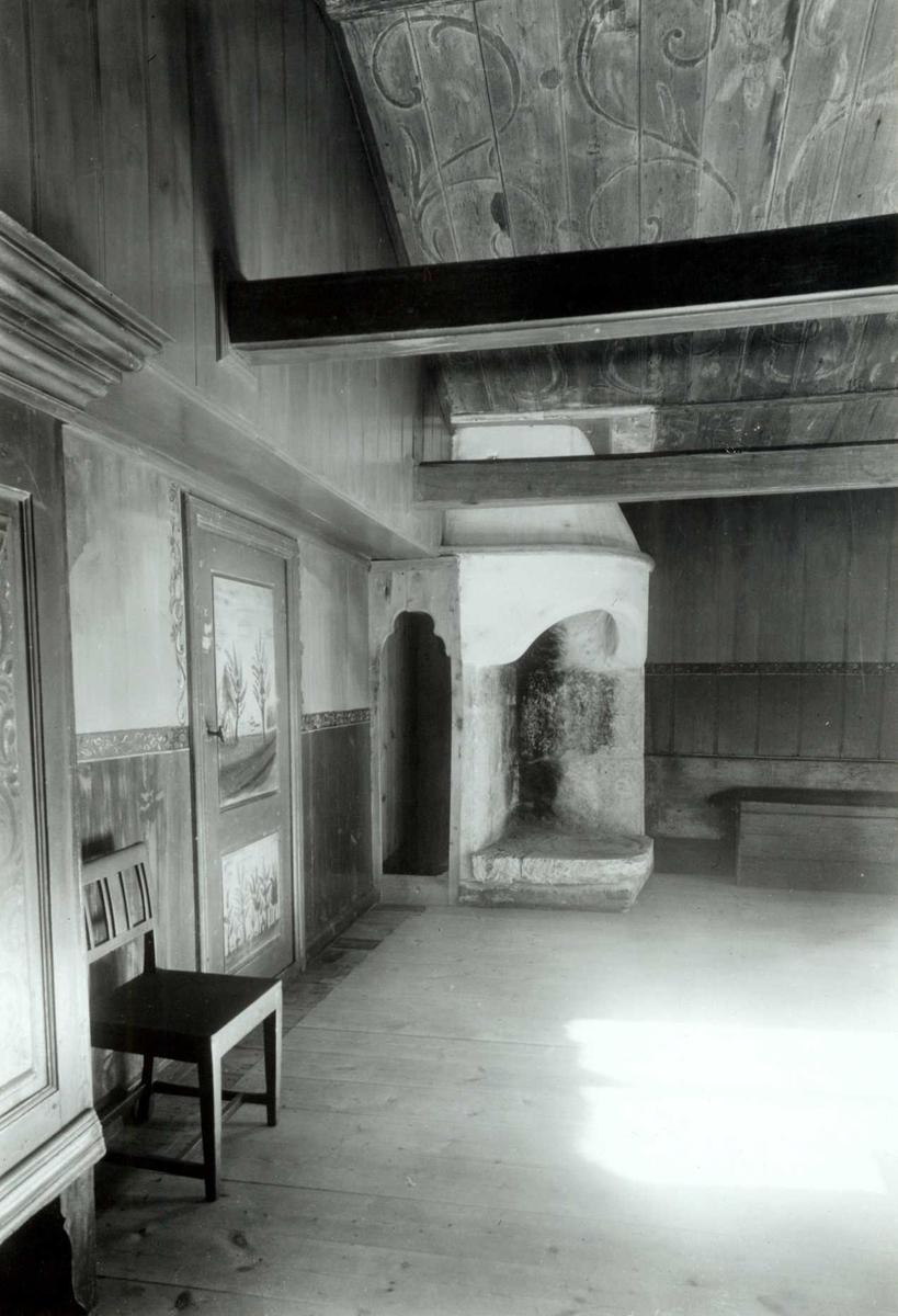 Olen, Øvre Steien, Alvdal, Nord-Østerdal, Hedmark. Interiør med peis, stol, dekorert tak og dekorerte dører. Nå på Glomdalsmuseet.