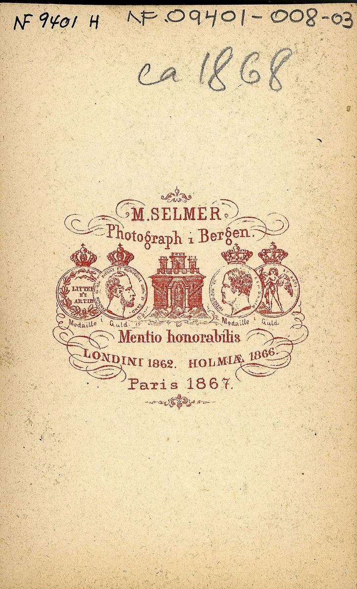 """25. Jentedrakter, kvinnedrakter, Kvinnherad. Portrett av 2 jente/kvinner med hodeplagg i fotoatelier med malt stueinteriør som bakgrunn. Den ene sitter og leser i en bok.  Fra serien """"Norske Nationaldragter"""" (nr.25), visittkortformat, håndkolorert. Serien er fotografert av fotograf Marcus Selmer (1819-1900), Bergen."""