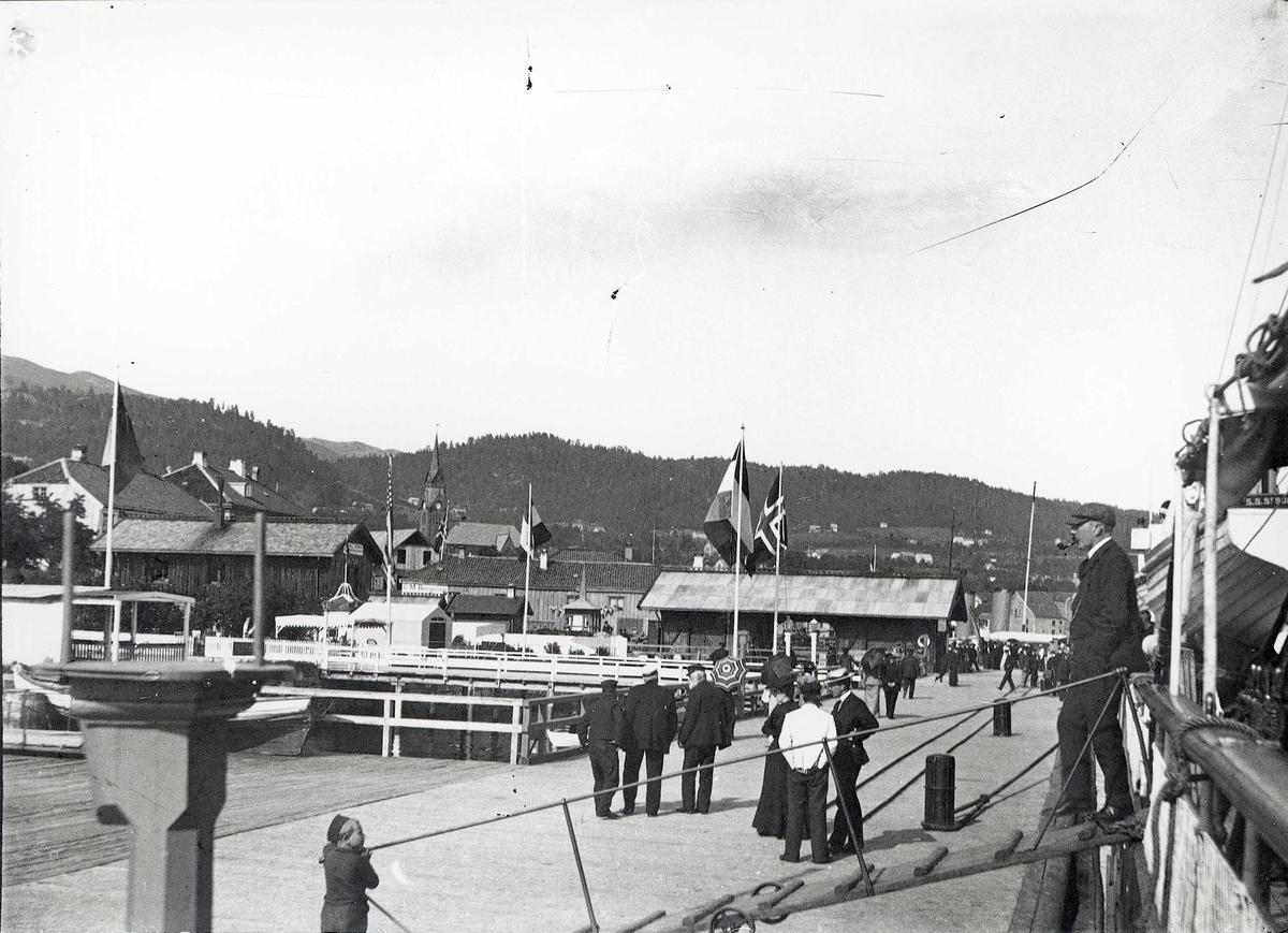 Fra havna i Molde, Møre og Romsdal. Flagg, mennesker på brygga og en mann går ned landgang.
