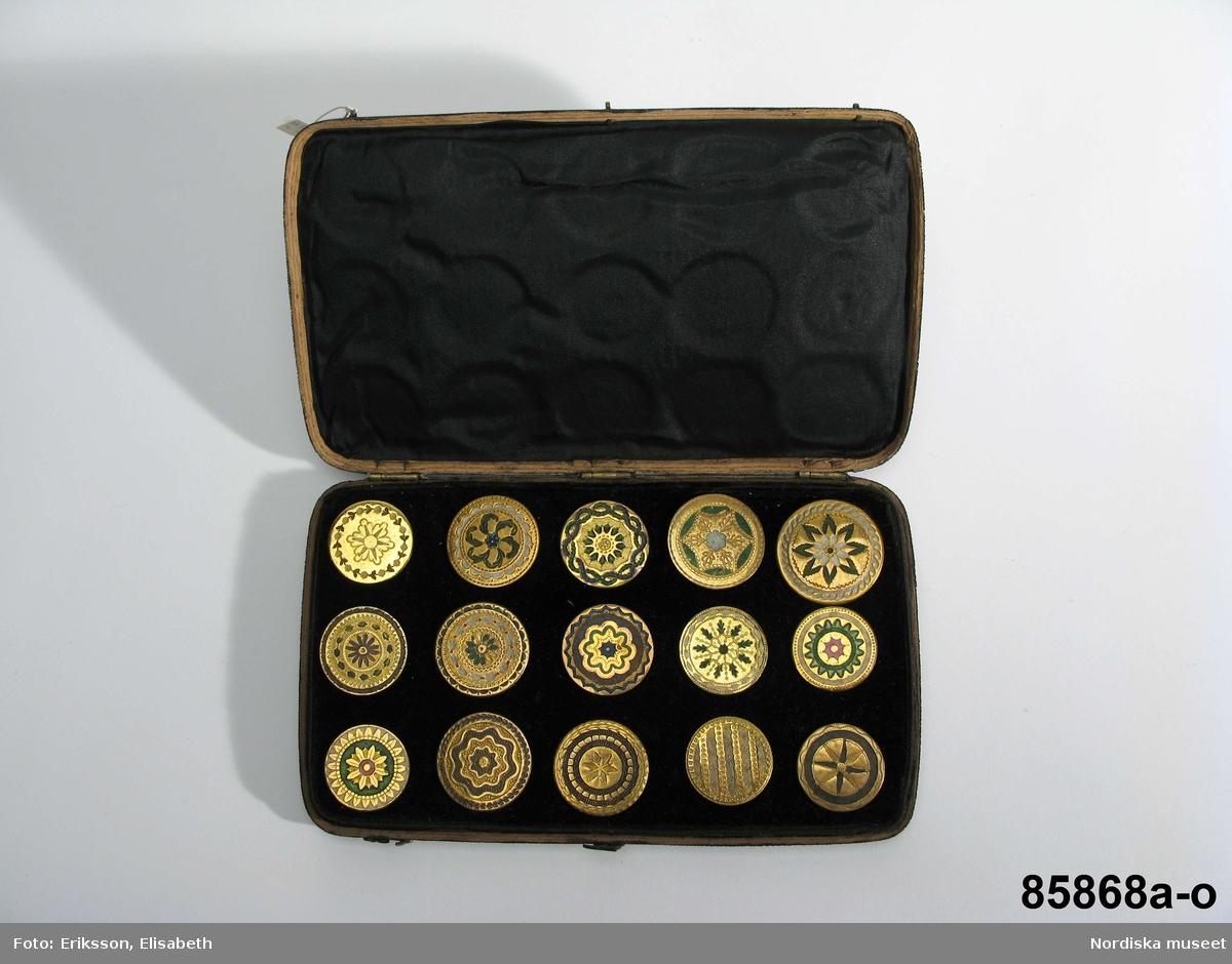 Runda flata knappar av mässing(?) med emaljerad dekor. Samt etui med plats för 15 knappar. A-Ö