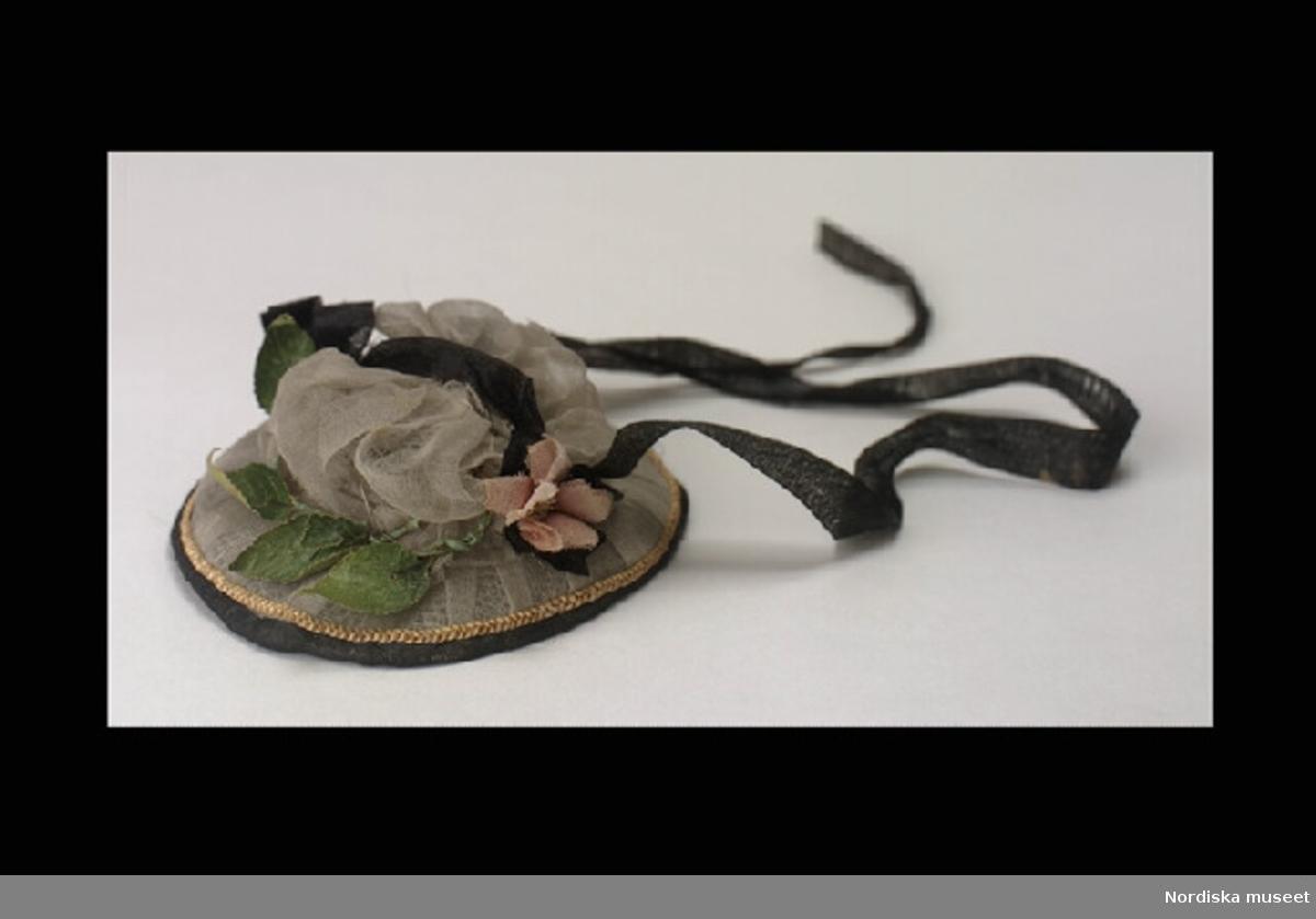 Inventering Sesam 1996-1999: Diam 10,0 (cm) Hatt, rund, liten kulle, stort brätte. Klädd med linong, dekorerad med svarta sidenband, pappersblommor och utmed brättet en halmfläta, invändigt klädd med tyll. Hör till docka inv.nr 127.730, tillsammans med kläder 127.731-127.745 Charlotta Dobson Hoffman sep 1997