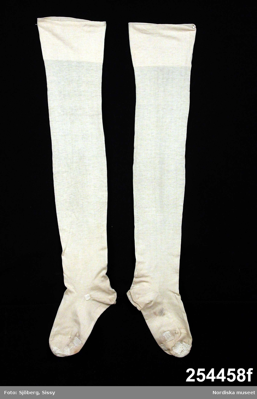 Hel husmorsdräkt a-g.  a. Klänning b. Midjeförkläde c. Halskläde d. Stycke e. Bindmössa f. Strumpor g. Nål  a. Klänning, längd 115 cm, vidd 212 cm, av rutig bomullslärft, röda och svarta ränder och tvärränder mot vit botten, avskuren i midjan, 2 ryggstycken, fram-och sidstycken skurna i ett, passepoaler i sömmarna. Knäppning fram med 6 handmålade porslinsknappar med linneor mot blå botten, signerade MA 1943 = Magda Angelin, Växjö. Tränsade knapphål. Kjolen veckad vid livet. Lång isydd ärm med linning. b. Midjeförkläde av vitt sildukslinne. c. Halskläde trekantigt av vitt sildukslinne med knypplad kantspets, smal enkel utdragssöm samt rutor i hopdragssöm. d. Stycke till mössan av vitt sildukslinne med knypplad kantspets och smal enkel utdragssöm. e. Bindmössa av blått konstsidenatlas med stor nackrosett. f. Strumpor ett par av vit merceriserad bomull.  Anskaffat av fru Valborg Andersson f. Magnusson 1896-1957, under åren 1944-45. Modellen var given men bomullstyget i klänningen kunde vara valfritt rutigt eller randigt. Tyget köptes i Kronobergs läns hemslöjdsförening i Växjö. Svarta pumps bars till dräkten. Bars vid sammankomster i Alvesta Husmorsförening.  Berit Eldvik juli 2005
