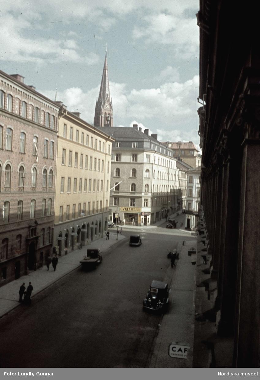 Stockholm. Döbelnsgatan mot Tegnérgatan med de östra husfasaderna och parkerade bilar utefter gatan. I bakgrunden Johannes kyrka.
