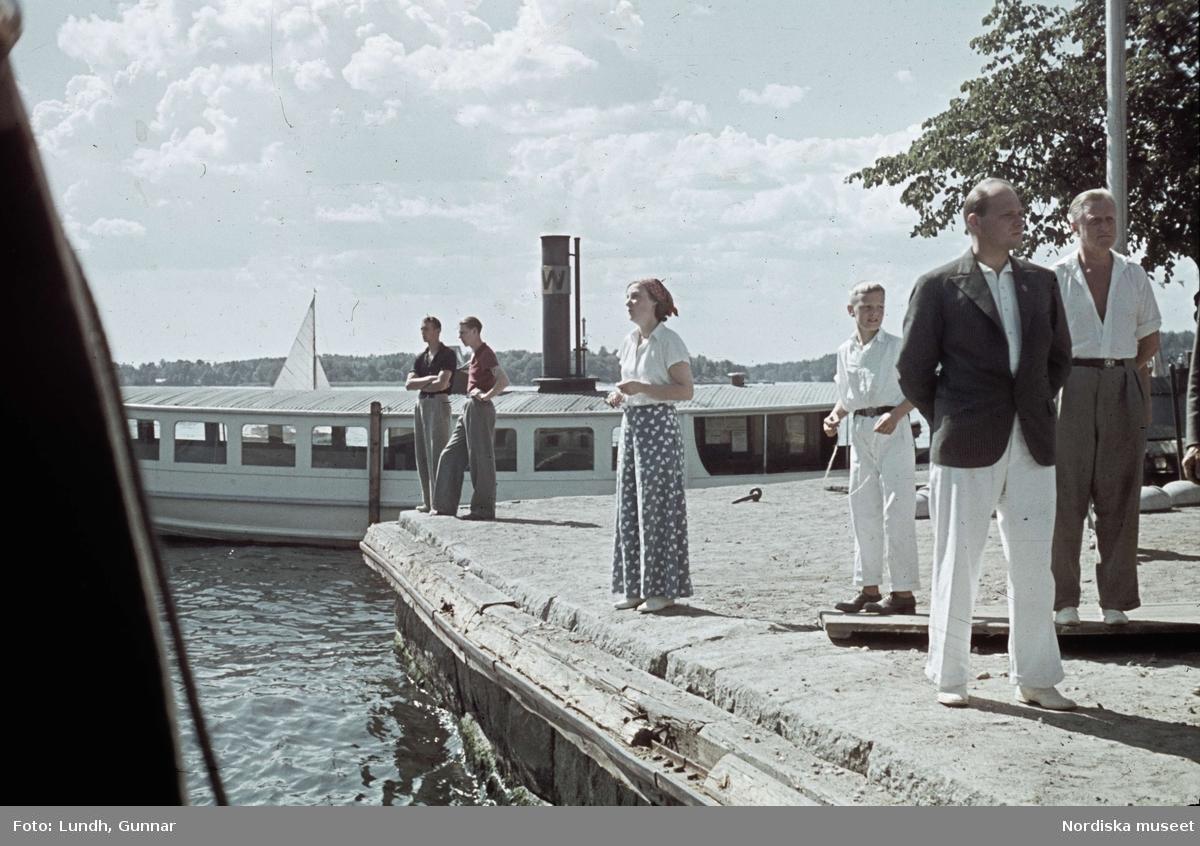Söderhamn i Vaxholm, hörnet Hamngatan/Strandgatan. Sommarklädda människor på kajen och i bakgrunden en vaxholmsbåt.
