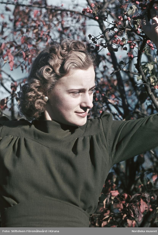 Kvinna i mörk klänning med lockig frisyr håller i trädgren.