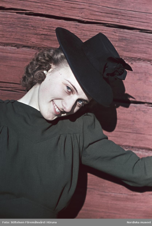 Kvinna i mörk klänning med lockig frisyr och hatt står framför rödmålad timmervägg.
