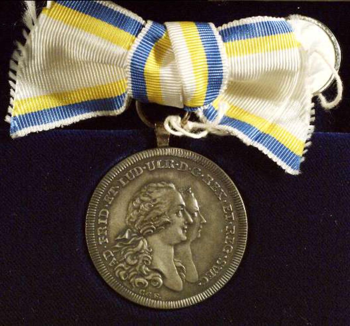 Framsidan av medaljen med Adolf Fredrik och Lovisa Ulrikas bilder i profil.