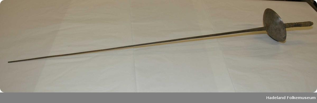 Kårde,  av jern, firekantet. Handtak av tre, viklet med linsnorer. Firekantet blad, butt i  enden, skinn inni bulen.  Ant. fra 1600-tallet.