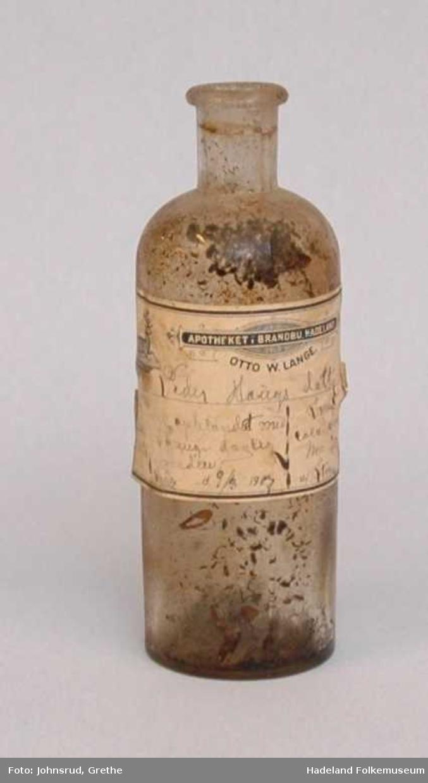 Flaske av glass med etikett.