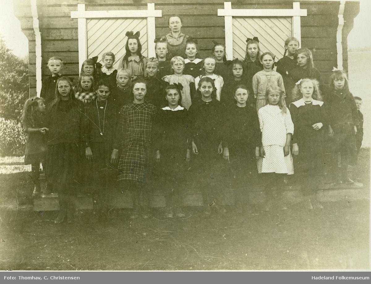 Skolebilde Lundby skole. Jenter fra tre klasser og lærerinne Martha Ruden oppstilt foran stabbur