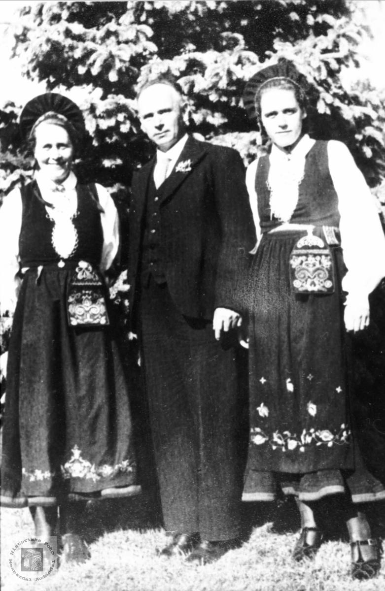 Portrett av bunadkledde damer med mann og far i midten. Audnedal