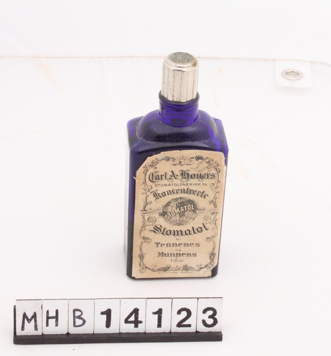 Firkantet, mørk blå glassflaske med metallkortk øverst. Det er papiretiketter på flaskens for- og bakside med påtrykket tekst. Forsiden har grafiske dekorelementer i nyrokokko og trykket sort tekst på hvit bunn. På baksiden er omtale av produktet og bruksanvisning. Bunnen har integret tekst i form av en påskrift.
