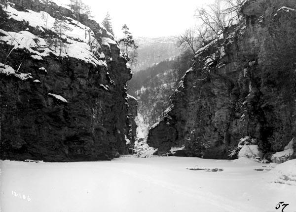 Loholet [i eldre dokumenter kalt «Lohullet»] i elva Vinstra i Nord-Fron kommune i Oppland. Dette vassdraget renner inn i Gudbrandsdalslågen fra vest.  Snaut to kilometer fra utløpet passerer Vinstra et trangt gjel mellom to bratte berghammere før vannmassene faller kvitskummende utfor en ni meter høy foss, Vinsterfossen.  I denne passasjen hadde tolv alen lange tømmerstokker lett for å sette seg fast om de fikk drive inn mellom bergveggene på tvers.  Slike stokker ble gjerne liggende som stengsel for tømmer som kom flytende etterpå, og kombinasjonen av strid strøm, stupbratte elvebredder og en strid foss gjorde det både vanskelig og farlig å få løsnet slikt tømmer.  Derfor var det nok ikke bare da dette fotografiet ble tatt, i 1906, at tømmeret ble liggende til vinteren kom med kulde, is og lav vannføring.  Vinstra ble likevel regnet som et noenlunde «sikkert» fløtingsvassdrag i den forstand at tømmeret som ble levert ved denne elva vanligvis ble fløtet ut i Lågen og videre i løpet av en sesong.  Fløtinga fra Slangen i Skåbu og ned til Lågen i hoveddalføret skal vanligvis ha tatt 8-10 dager.  Siste ordinære fløtingssesong i Vinstraelva ser ut til å ha vært 1966, men det ble liggende igjen noen småkvanta som ble tatt året etter.  Dette fotografiet later til å være tatt fra øst mot vest, altså i motstrøms retning.  Førsteleddet i navnet Loholet refererer til garden Lo, som er en av de større landbrukseiendommene i området.