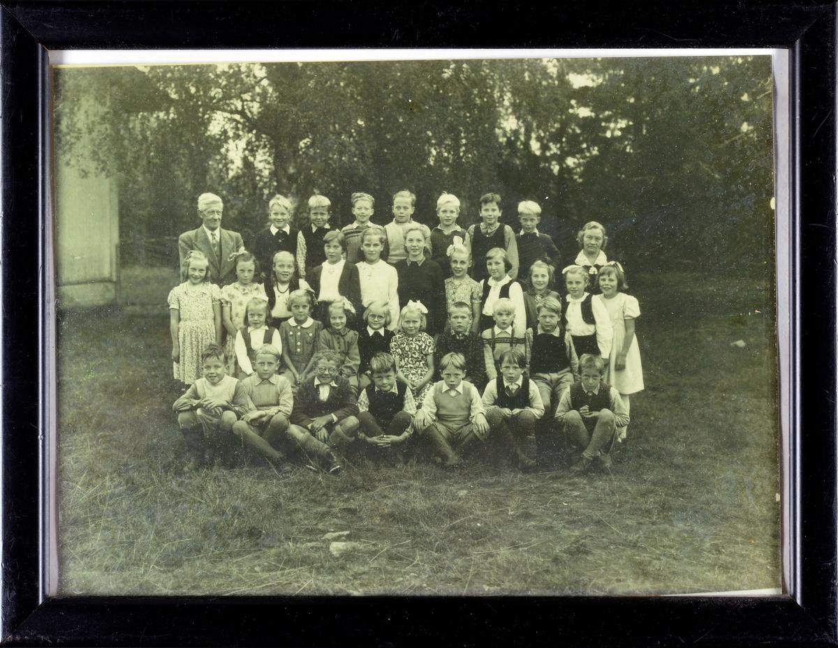 Skoleelever med lærer ute, med litt av skolebygningen i bakgrunnen