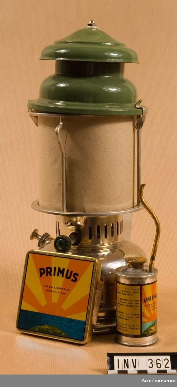 """Består av en glödnätslykta (fabrikat Primus 1020); en säkerhetskanna för tändsprit; en ask innhållande reservdelar; samt en papperspåse med glödstrumpa.  Asken är märkt """"Primus B.A. Hjorth & Co A/B"""", och påsen """"Optimus 300 C.P. No. 300""""."""