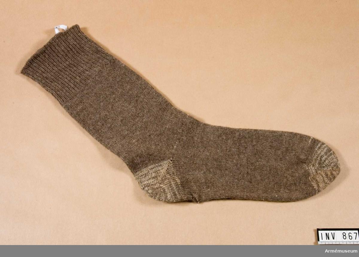 Stl: skonr 44. Yllesocka (strumpa) med stickad mudd. Hela skaftets  höjd 300 mm. Mudden är resårstickad, en avig-en rät. Övriga strumpan slätstickad. Häl- och tåintagningarna är förstärkta med ljusare tråd av nylon (?).