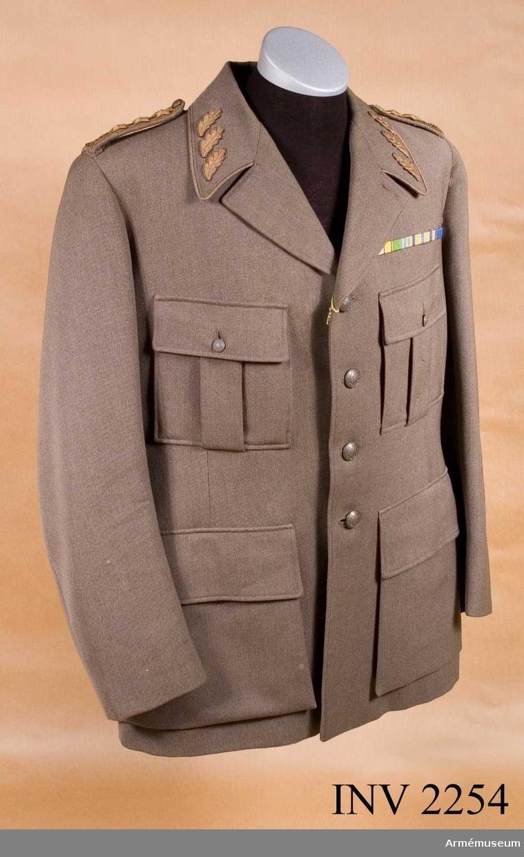 Stl B 152. Namnchiffer m/1943 och gradbeteckning för general i form av tre broderade bronsstjärnor på matta av generalsgalon i bronsfärg m/1939. På kragsnibbarna tre broderade eklöv m/1939. Knappar  generalitets / generalstabens m/1939. Enkelradig, blusartad, av  gråbrungrönt yllediagonal. Utan livsöm. Mjuk och nedvikt krage.  Slag som kunna bäras hop- eller uppknäppta. Utsydda bröstfickor  med raka lock och bälgar, vardera knäppta med en liten knapp  m/1939 för vilka finns motsvarande knapphål i ficklocken.  Lockens överkanter är horisontella och sitter i jämnhöjd med översta knappen i framvådens knapprad. Utsydda sidfickor med  raka lock. Överkanterna är horisontella och sitter ca 5 mm  nedanför nedersta knappen i framvådens knapprad. En innerficka i vänster sida. Sprund i ryggen börjar ca 20 mm under midjan.  Två intag i ryggen - ett på vardera sidostycket som vid behov kan öppnas. Rocken är helt fodrad. Axelklaffar 40 mm breda, som  knäppes fast på axeln med en liten knapp m/1939. Rocken knäpps  med fyra stora knappar m/1939 på högra framvåden.